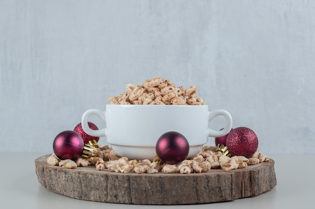Un piatto di legno pieno di cereali sani con palline di natale.
