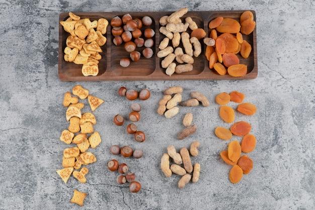 Piatto di legno pieno di noci, cracker e albicocche secche sulla superficie in marmo.