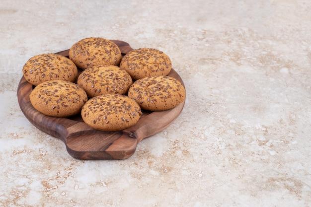 Piatto di legno pieno di biscotti di farina d'avena sulla superficie in marmo.