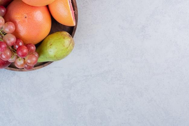 Деревянная тарелка, полная свежих органических фруктов. на сером фоне.