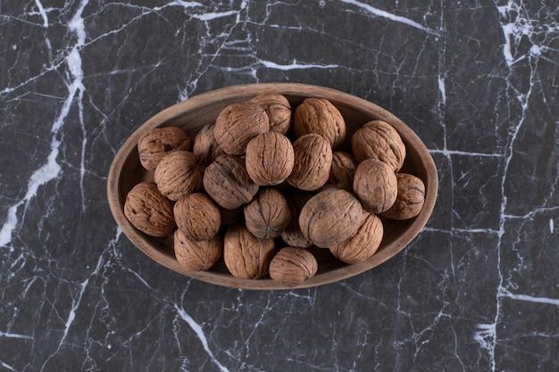 Деревянная тарелка, полная свежих грецких орехов в скорлупе на мраморе.