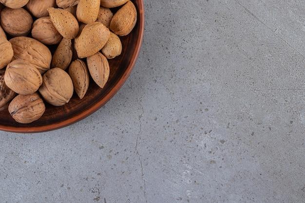 건강한 견과류가 가득한 나무 접시는 돌 배경에 놓여 있습니다.