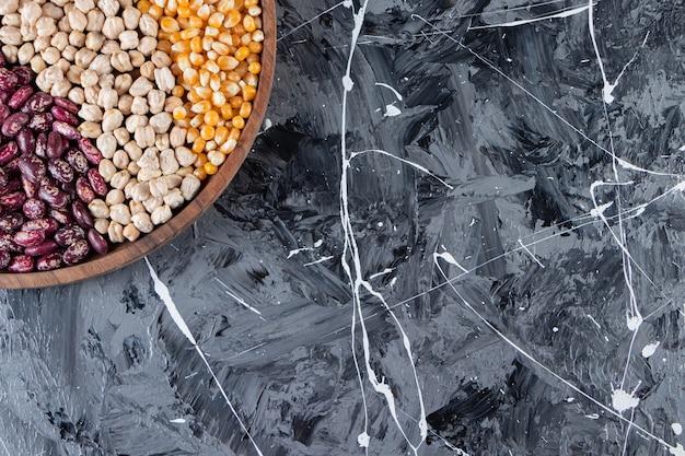 Деревянная тарелка, полная сырых зерен, гороха и бобов на мраморном фоне.