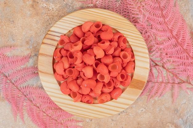Un piatto di legno pieno di maccheroni rossi non preparati.