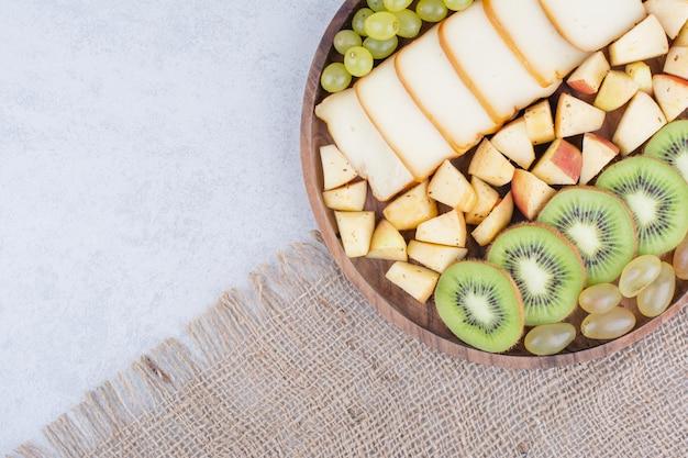 Un piatto di legno pieno di frutta e pane a fette