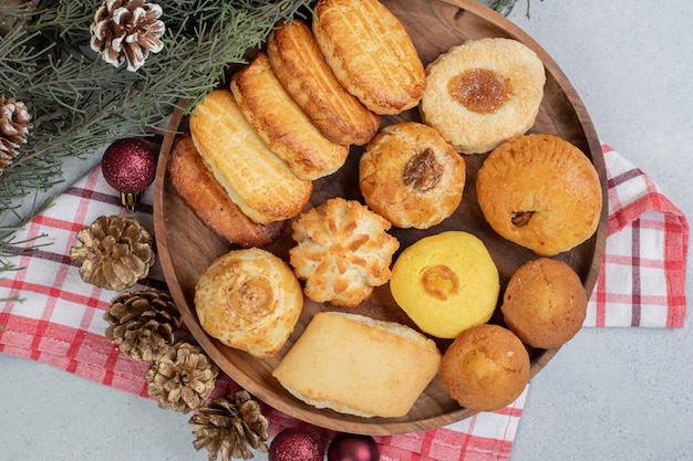 A wooden plate full of sweet pastries with christmas balls and pinecones.