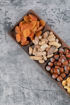 Wooden plate full of various nuts, crackers and dried apricots on marble surface.