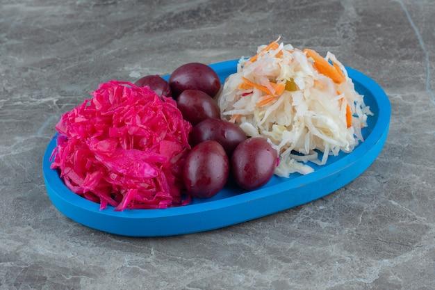 Деревянная тарелка с розовой, квашеной капустой и пальмами.