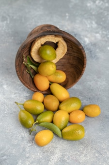 A wooden plate full of yellow fresh kumquats with leaves on a marble .