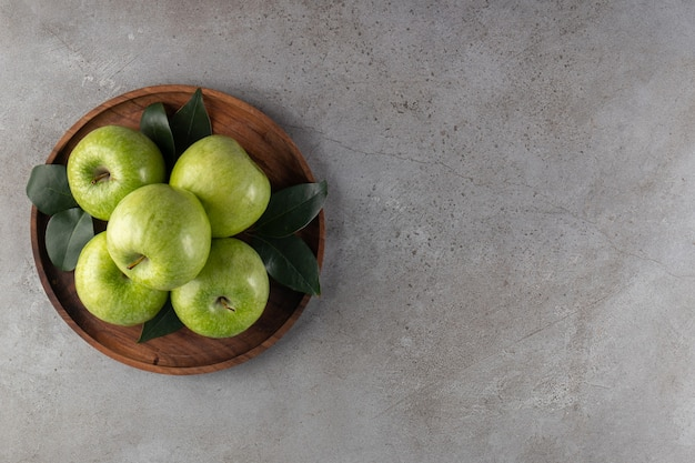 Wooden plate of green apples placed on stone background.
