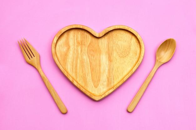 ピンクの表面にスプーンとフォークでハートの形をした木の板。上面図