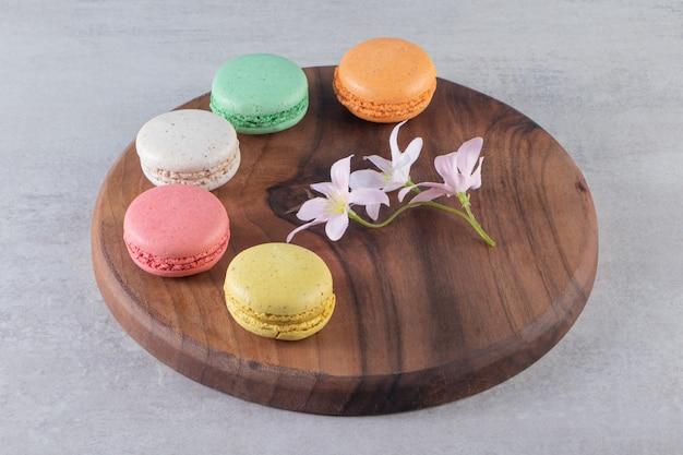 石のテーブルに花とカラフルな甘いマカロンの木のプレート。