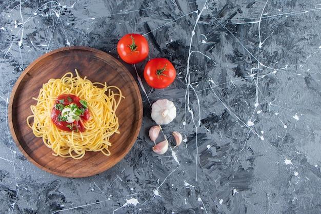 Деревянная тарелка вкусных спагетти с томатным соусом и овощами на мраморной поверхности.