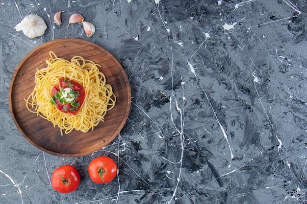 대리석 표면에 토마토 소스와 야채를 곁들인 맛있는 스파게티 나무 접시.