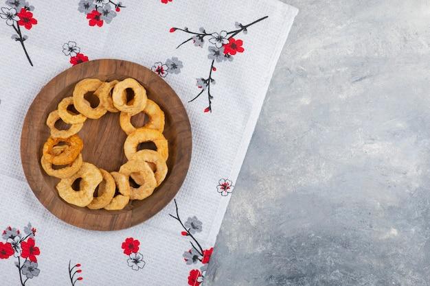 말린 된 사과 링의 나무 접시는 흰색 식탁보에 배치.