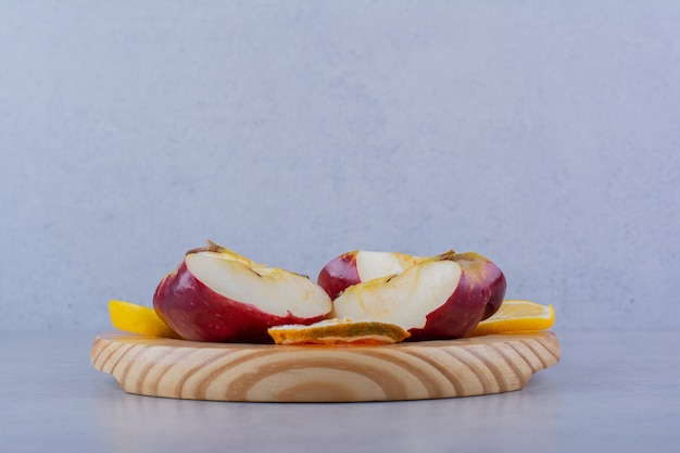 신선한 사과 돌 테이블에 레몬 조각 나무 접시.