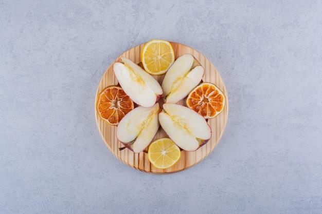 Деревянная тарелка свежих яблок и ломтиков лимона на камне.