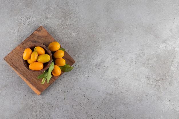 Деревянная тарелка свежих сочных кумкватов на каменной поверхности