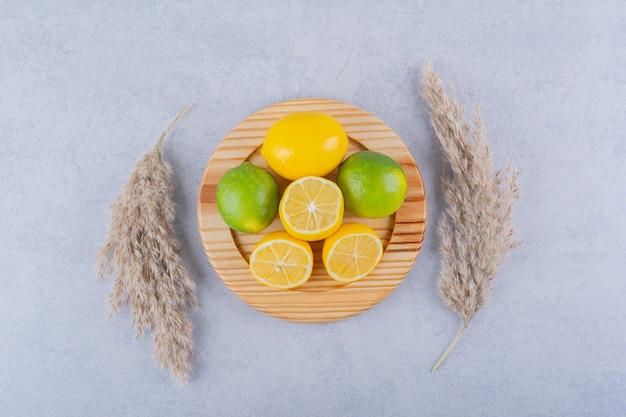 Деревянная тарелка свежих сочных лимонов на каменном столе.