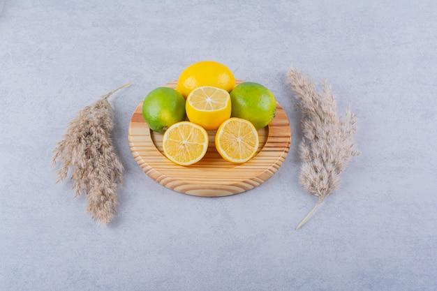 Деревянная тарелка свежих сочных лимонов на камне.