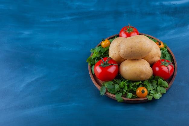 신선한 감자와 토마토 블루 테이블에 나무 접시.