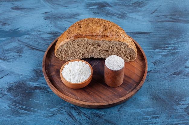 Деревянная тарелка разрезанного пополам ржаного хлеба с миской муки на синей поверхности.