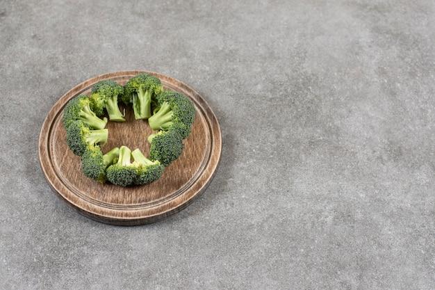 Деревянная тарелка здоровой свежей брокколи на каменной поверхности.