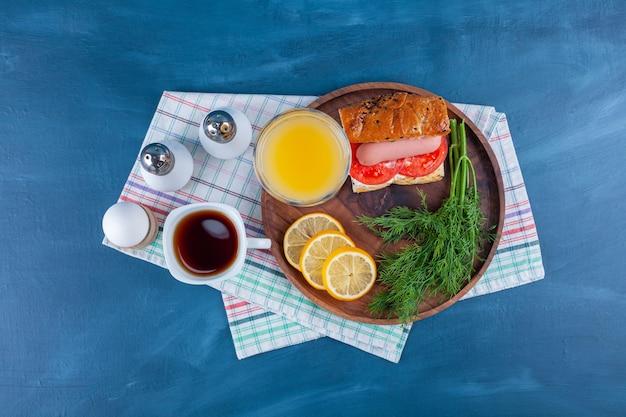 Деревянная тарелка домашнего свежего сэндвича и стакан сока на синей поверхности.