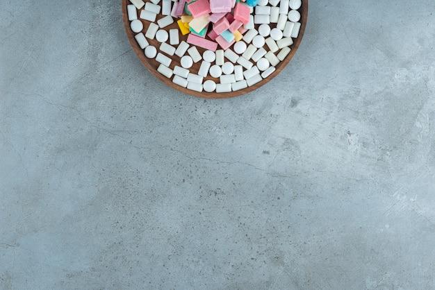돌 표면에 많은 껌의 나무 접시.