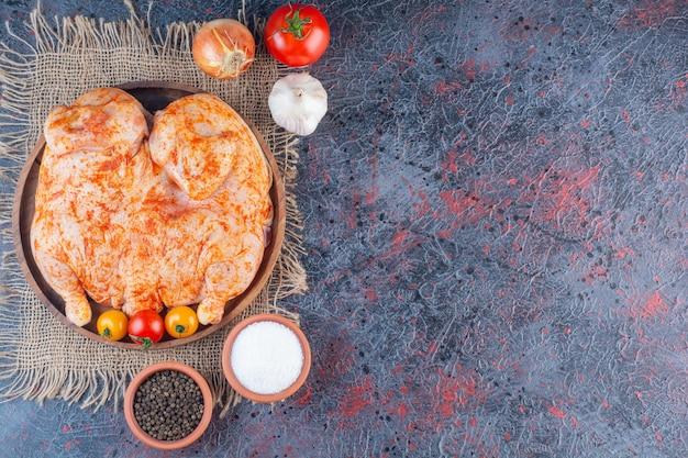 Деревянная тарелка маринованной целой курицы на мраморной поверхности.