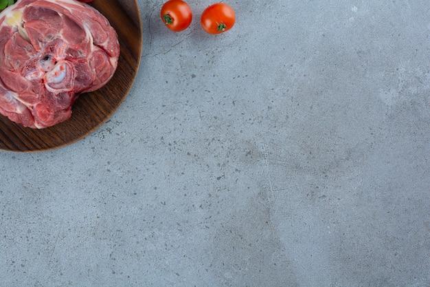 石のテーブルの上の生の牛肉ステーキの木のプレート。