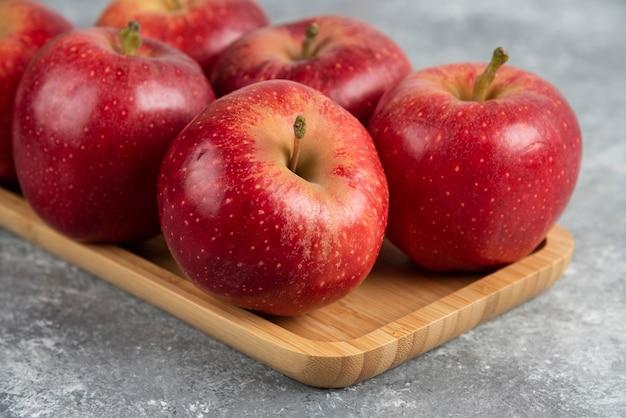 대리석 테이블에 빛나는 빨간 사과 나무 접시. 무료 사진
