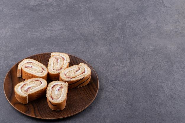 돌 테이블에 썰어 스폰지 롤 케이크의 나무 접시.