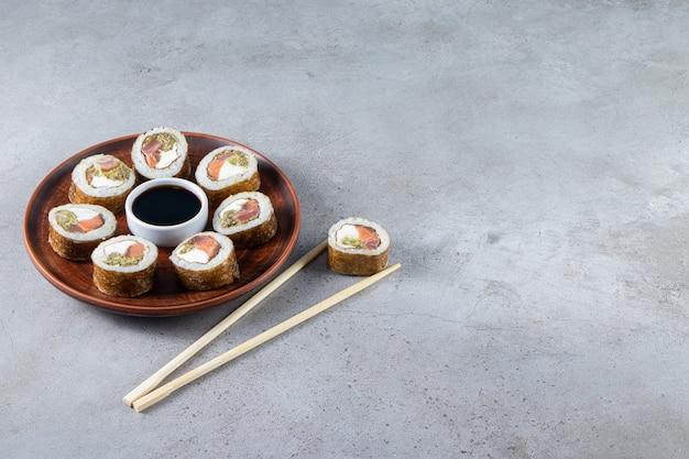Деревянная тарелка суши-роллов с тунцом на каменном фоне.