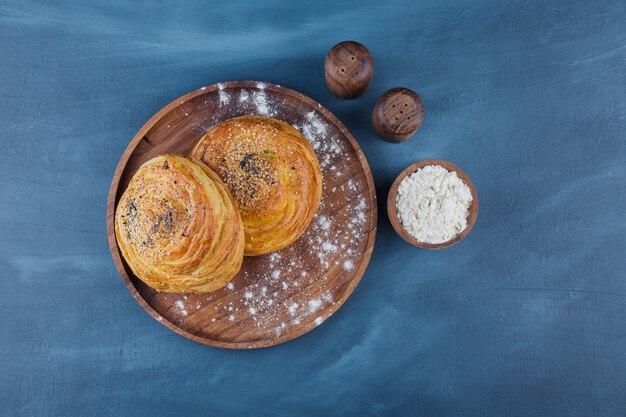 파란색 표면에 씨앗과 달콤한 파이의 나무 접시.