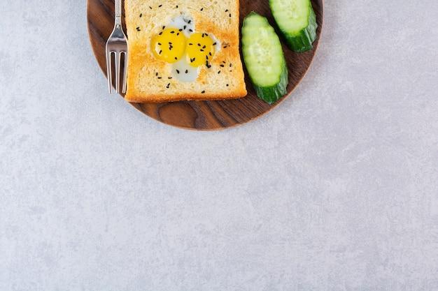 目玉焼きとキュウリをテーブルに置いたトーストの木のプレート。