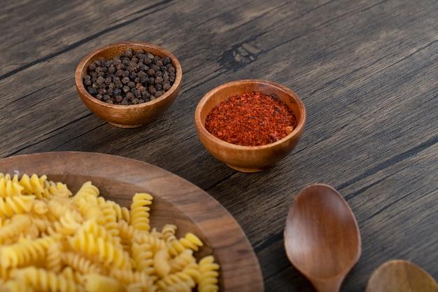 Деревянная тарелка сырых макаронных изделий фузилли и специй на деревянной поверхности.