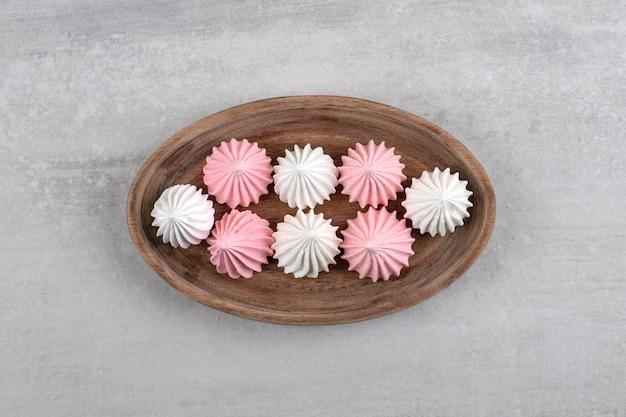 Деревянная тарелка десерта из белого и розового безе на каменной поверхности.