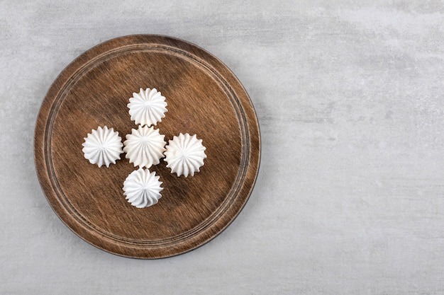돌 테이블에 흰 머 랭 디저트의 나무 접시.