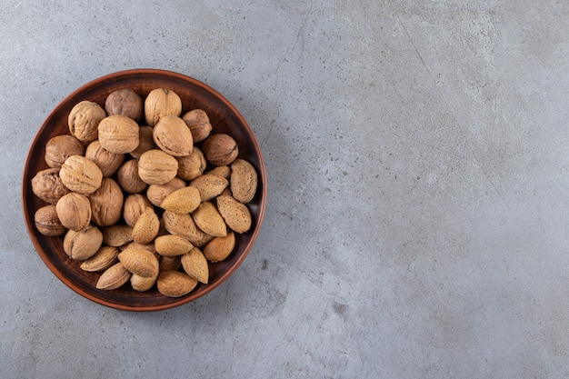 Wooden plate of organic shelled walnuts and almonds on stone background.