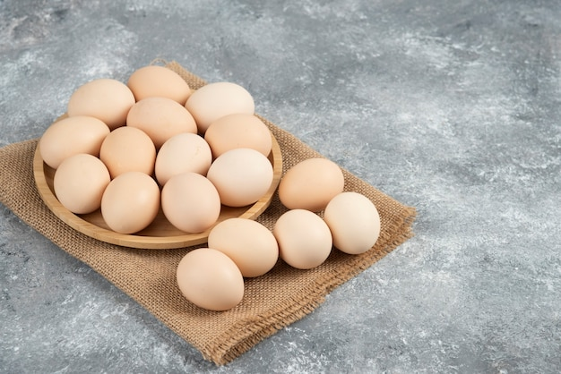 Wooden plate of organic uncooked eggs on marble surface.