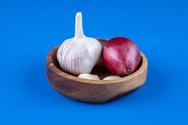 Wooden plate of purple onion and garlic on blue surface