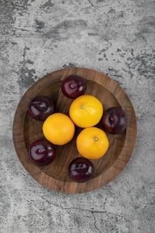 Un piatto di legno di prugne viola e limoni freschi sul tavolo di pietra.