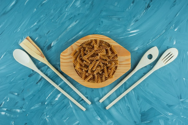 Wooden plate of raw dry fusilli on marble surface