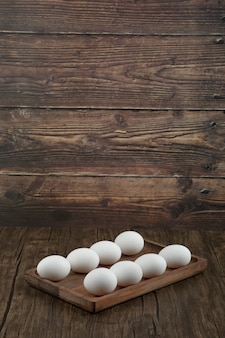 Wooden plate of raw white eggs on wooden table.