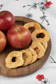 Wooden plate of red apples and dried rings on tablecloth.