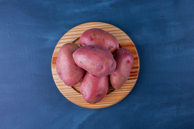 Wooden plate of ripe sweet potatoes on blue surface.