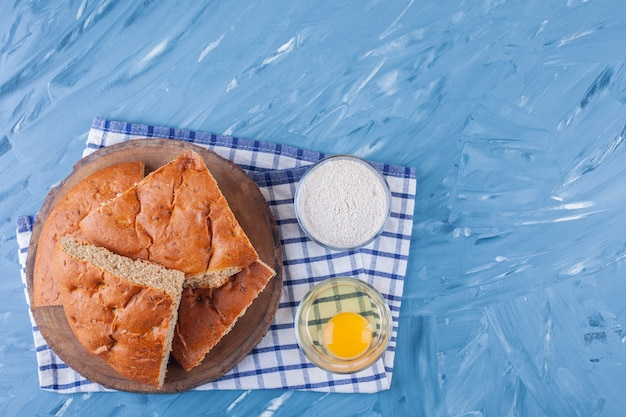 Wooden plate of sliced bread, egg yolk and flour on blue surface.