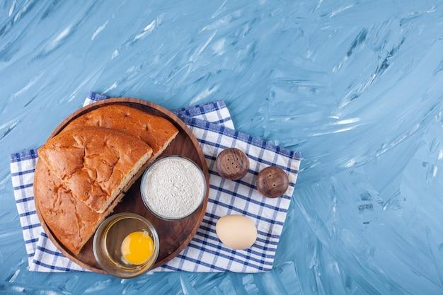 Piatto di legno di pane a fette, tuorlo d'uovo e farina sulla superficie blu.