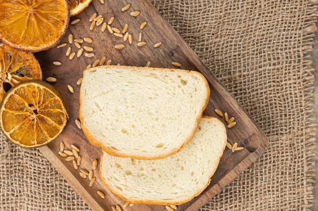 Wooden plate of sliced bread with orange and barley on burlap.
